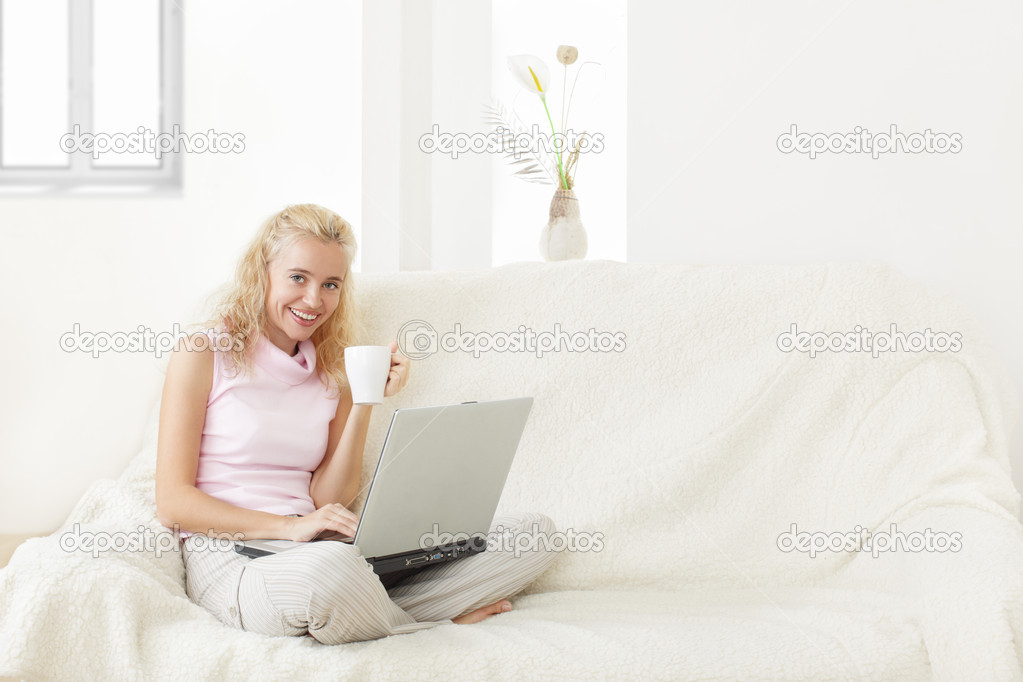 Young woman with laptop on a sofa — Stock Photo #2405354