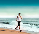 Young woman jogging on the beach — Stockfoto
