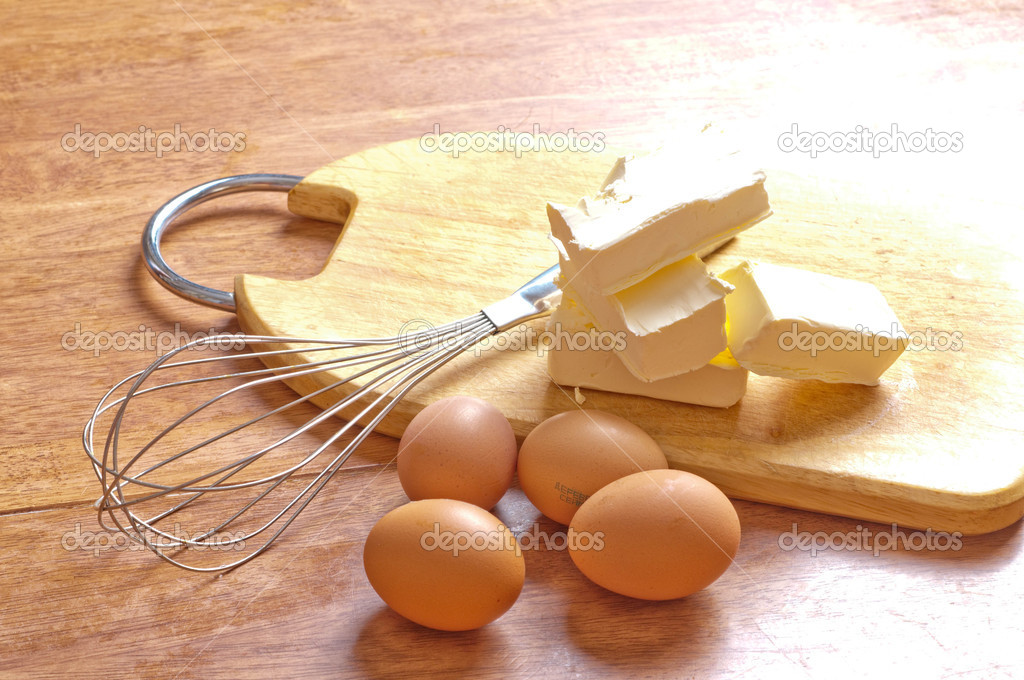 Baking ingredients with eggbeater and cake tin on a wooden kitchen-board  Stock Photo #2086614