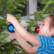 The boy dresses up Christmas tree — Stock Photo