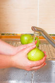 The woman washes a green apple — Stock Photo