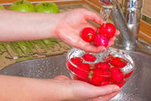 The girl washes a radish — Stock Photo