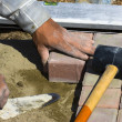 Worker puts sidewalk tile - Stock Photo