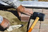 Pracovník klade dlaždic chodníku — Stock fotografie