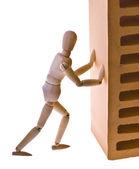Uomo di legno con un mattone — Foto Stock