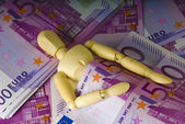 Wooden man sleeps under a money — Stok fotoğraf