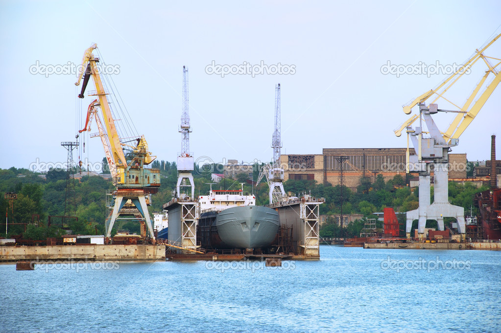 Shipbuilding cranes and some sea ships near a pier — Stock Photo #1642233