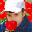 Pretty child with red tulips — Stock Photo