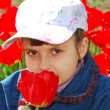 Pretty child with red tulips — Stock Photo #1681561
