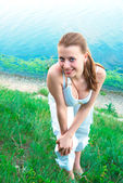 Pretty girl on river shore behind — Stock Photo