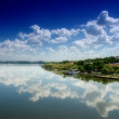Cloudy blue sky reflection in calm water — Stock Photo #1759885