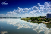 Cloudy blue sky reflection in calm water — Stock Photo