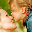 Girl kisses mum on nose - Stock Photo