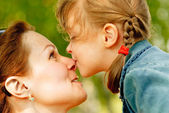 Girl kisses mum on nose — Stock Photo