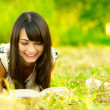 Girl reads book on meadow — Stock Photo #1596864