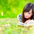 Girl reads book on meadow — Stock Photo