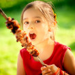 Girl eats kebab - Stock Photo