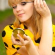 Blonde with mirror and ink for eyelashes — Stock Photo #1596921