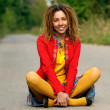 Girl with dreadlocks sits on asphalt — Stock Photo