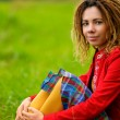 Girl with dreadlocks sits on grass — Stock Photo
