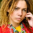 Girl  with dreadlocks speaks on phone — Stock Photo