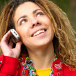 Girl with dreadlocks speaks by phone - Stock Photo