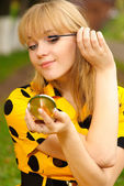 Blonde with mirror and ink for eyelashes — Stock Photo