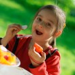 Girl eats a tomato and a garden radish - Stock Photo