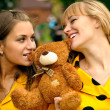 Girlfriends with toy bear cub — Stock Photo