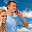 Girl and guy speak by mobile phone — Stock Photo #1609065