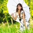 Girl under sun-protection umbrella - Stock Photo