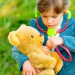 Girl listens stethoscope to plush bear - Stok fotoraf