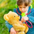 Girl listens stethoscope to plush bear — Stock Photo