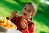 Girl eats a tomato and a garden radish — Stock Photo