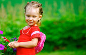 Girl with a backpack about florets — Stock Photo