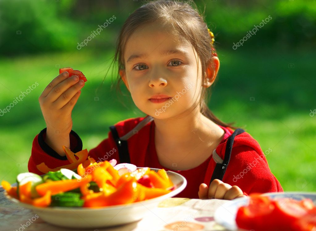 The little girl sits at a table in garden of parents and eats cut vegetables. — Stock Photo #1602315