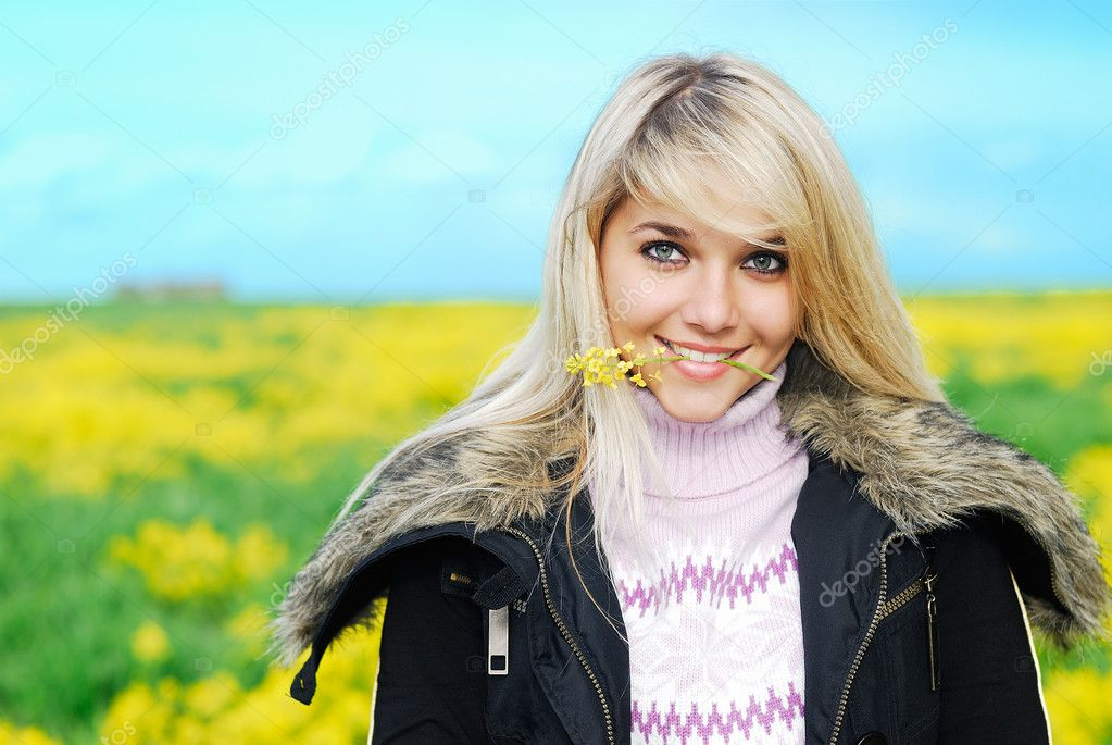 Young beautiful woman holds in  teeth a yellow floret against meadow and the sky  Stock Photo #1602333