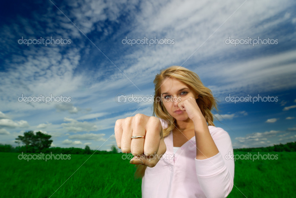 The young beautiful woman beats a fist towards to  camera against  nature  Stock Photo #1602428