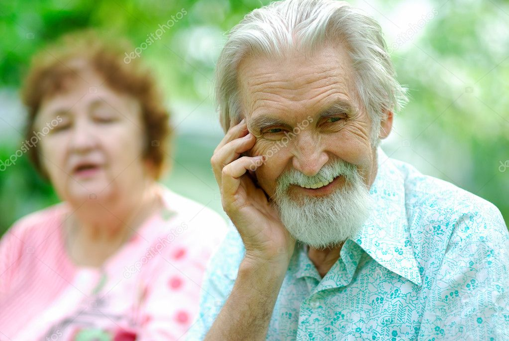 Old man laughs, as his wife has told an interesting ridiculous joke.  Stock Photo #1607786