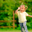 Foto Stock: Little girl runs across field