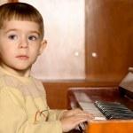 Boy plays piano — Stock Photo