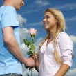 The young man gives a rose to girl — Stock Photo