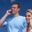 Girl and guy speak by a mobile phone — Stock Photo