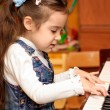 Girl plays piano - Stock Photo