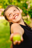 Laughing girl stretches an apple — Stock Photo