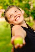 Smějící se dívka roztáhne jablko — Stock fotografie