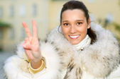 Girl in fur coat shows victory — Stock Photo
