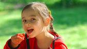 Girl eats tomato — Stock Photo