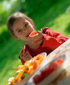 The girl eats a tomato — Stock Photo