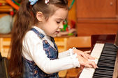 Girl plays piano — Stok fotoğraf